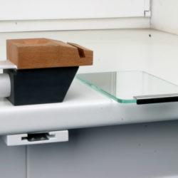 Под столешницей показана деталь, которая крепится к низу столешницы зуботехнического стола, эта деталь и есть держатель финагеля